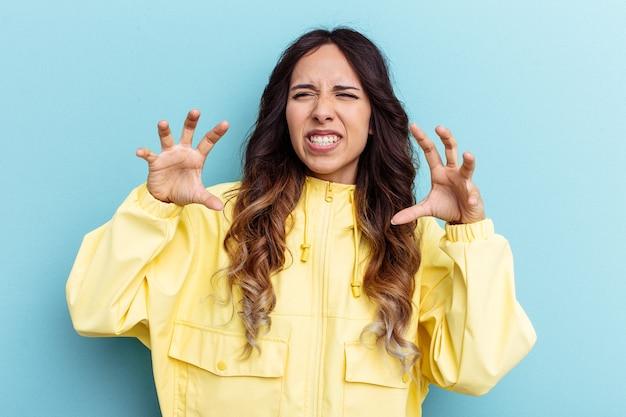 Giovane donna messicana isolata su sfondo blu che mostra artigli che imitano un gatto, gesto aggressivo.