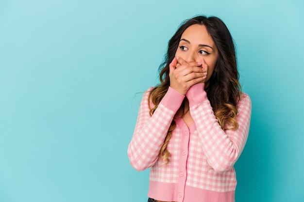 Giovane donna messicana isolata sulla parete blu premurosa che guarda ad uno spazio della copia che copre la bocca con la mano.