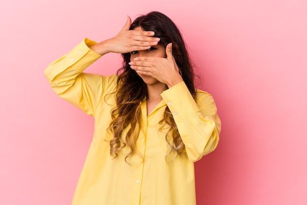 La giovane donna messicana isolata su sfondo rosa sbatte le palpebre alla telecamera attraverso le dita, imbarazzata che copre il viso.