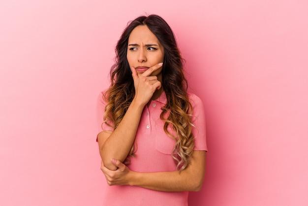 Giovane donna messicana isolata su sfondo rosa contemplando, pianificando una strategia, pensando al modo di fare affari.