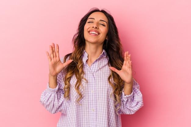 La giovane donna messicana isolata su sfondo rosa ride forte tenendo la mano sul petto.