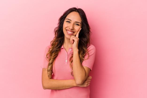Giovane donna messicana isolata su sfondo rosa sorridendo felice e fiducioso, toccando il mento con la mano.