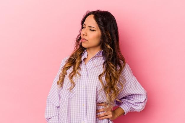 Giovane donna messicana isolata su sfondo rosa che soffre di mal di schiena.