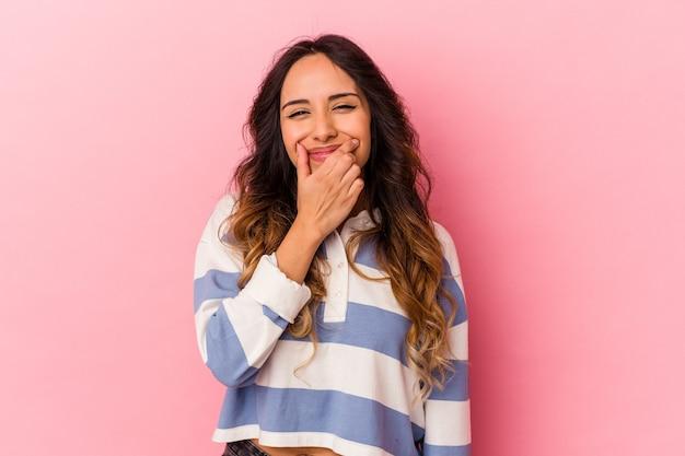 Giovane donna messicana isolata sul muro rosa dubitando tra due opzioni.