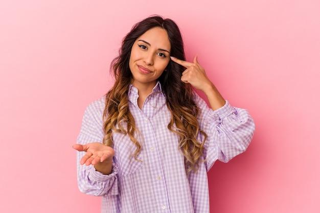Giovane donna messicana isolata sul muro rosa che tiene e che mostra un prodotto a portata di mano.