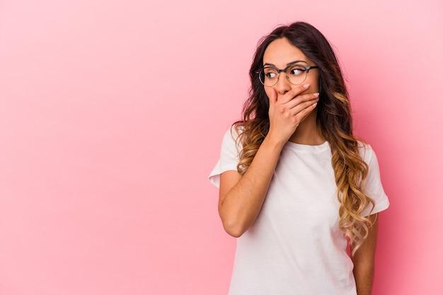 Giovane donna messicana isolata sulla parete rosa premurosa alla ricerca di uno spazio di copia che copre la bocca con la mano.