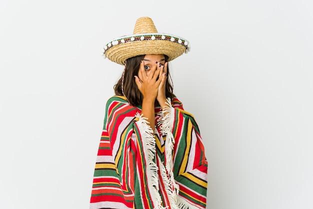 La giovane donna messicana isolata sul muro bianco sbatte le palpebre attraverso le dita spaventata e nervosa.