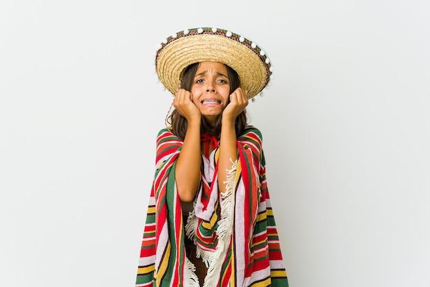 Giovane donna messicana isolata sul muro bianco piangendo, insoddisfatta di qualcosa, agonia e concetto di confusione