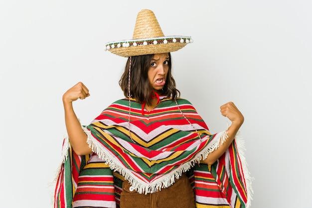 Giovane donna messicana isolata sul muro bianco che mostra il gesto di forza con le braccia, simbolo del potere femminile