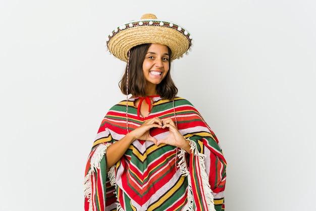 Giovane donna messicana isolata sulla parete bianca che sorride e che mostra una forma del cuore con le mani.