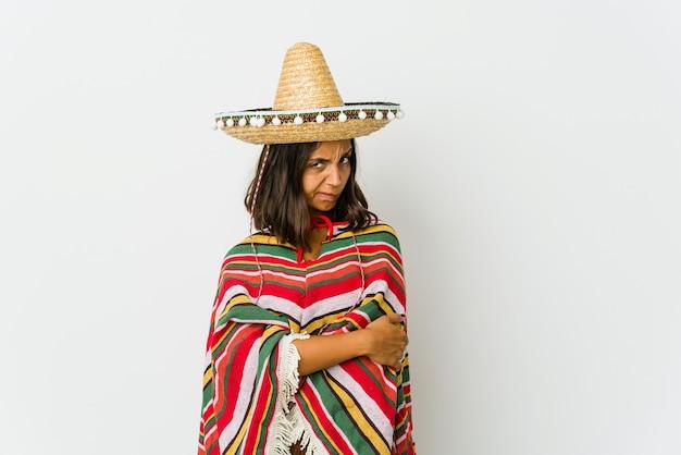 Giovane donna messicana isolata sul muro bianco infelice guardando davanti con espressione sarcastica
