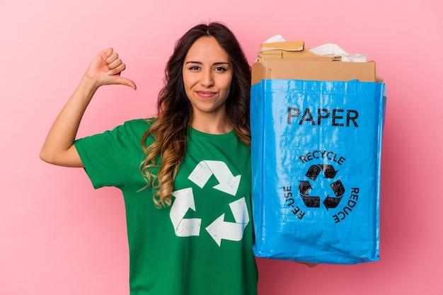 La giovane donna messicana che ricicla il cartone isolato su fondo rosa si sente orgogliosa e sicura di sé, esempio da seguire.