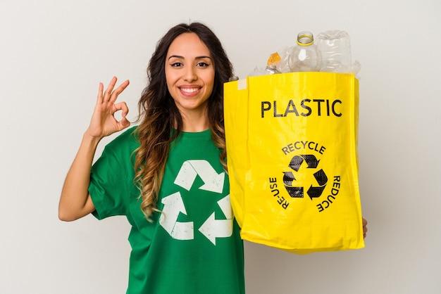 Giovane donna messicana che ricicla plastica isolata su fondo bianco allegro e fiducioso che mostra gesto giusto.