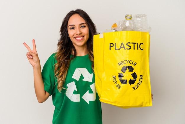 Giovane donna messicana che ricicla plastica isolata su sfondo bianco gioiosa e spensierata che mostra un simbolo di pace con le dita.