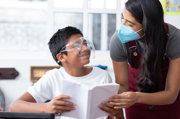 Giovane insegnante messicana e bambino in classe, con maschera facciale, concetto di educazione prescolare