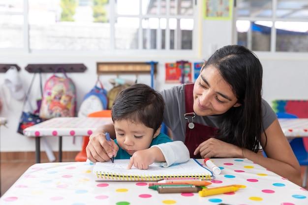 Giovane insegnante messicana e bambino nell'aula dell'asilo, concetto di educazione prescolare