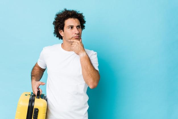 Giovane uomo di mezza età in possesso di una valigia guardando lateralmente con espressione dubbiosa e scettica.