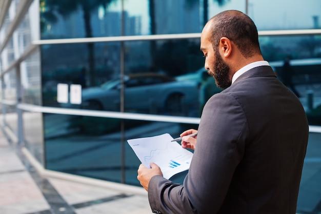 Giovane uomo d'affari mediorientale che legge i rapporti sui fondi