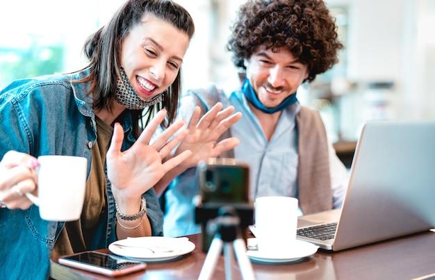 Giovane coppia millenaria condivisione di contenuti creativi con maschera facciale