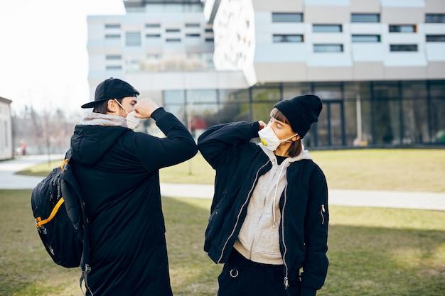 Giovane coppia millenaria che si tocca il gomito per proteggersi durante la pandemia di covid19, allontanamento sociale durante il coronavirus con persone per strada in abiti casual