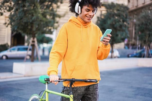 Giovane motociclista millenario che ascolta l'app musicale della playlist con l'app per cellulare in città - focus sul viso