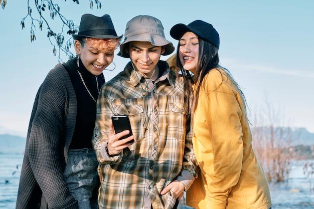 Giovani amici millenari che prendono un selfie con lo smartphone si abbracciano insieme in un parco al tramonto