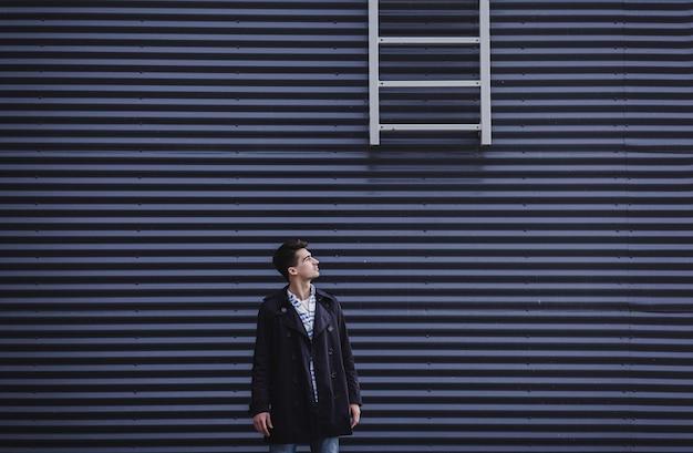 Giovane uomo millenario vestito di cappotto si erge contro il muro. spazio per il testo