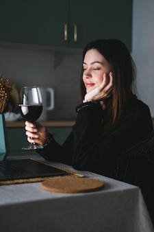 Giovane donna millenaria che ha videochiamata sul computer portatile e beve vino, usa la tecnologia per comunicare con amici o familiari