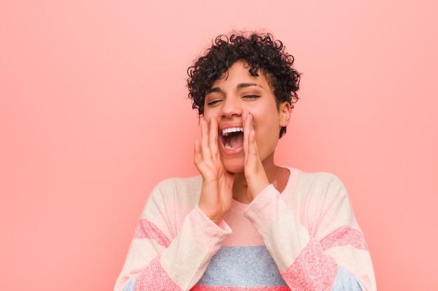 Giovane donna afroamericana mista dell'adolescente che grida eccitata alla parte anteriore.