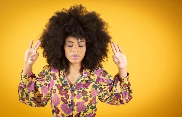 Giovane donna afroamericana mista con capelli afro, indossando casual rilassante e sorridente con gli occhi chiusi facendo meditazione