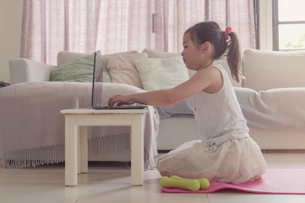 Giovane ragazza asiatica mista che guarda i video in streaming sul computer portatile, allenamento che si prepara a casa, classe online di esercizi di zoom, concetto di allontanamento sociale