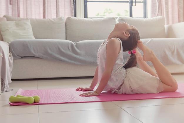Giovane allenamento misto asiatico della ragazza che si prepara a casa, facendo gli esercizi del pavimento del peso corporeo, guardando i video in streaming online sul computer portatile, concetto di allontanamento sociale