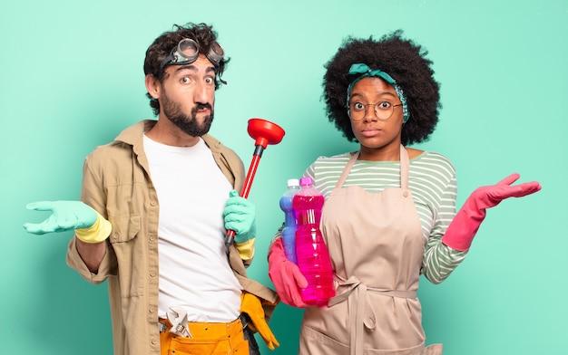 Giovane coppia mista che tiene oggetti per la pulizia in posa su turchese