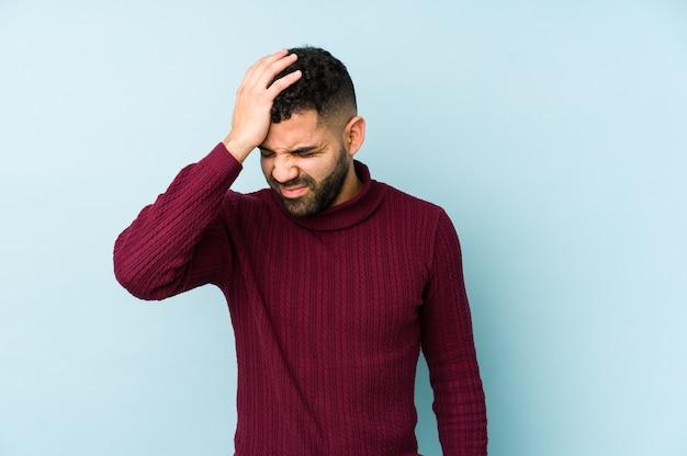 Giovane uomo arabo di razza mista isolato dimenticando qualcosa, schiaffi sulla fronte con il palmo e chiudendo gli occhi.
