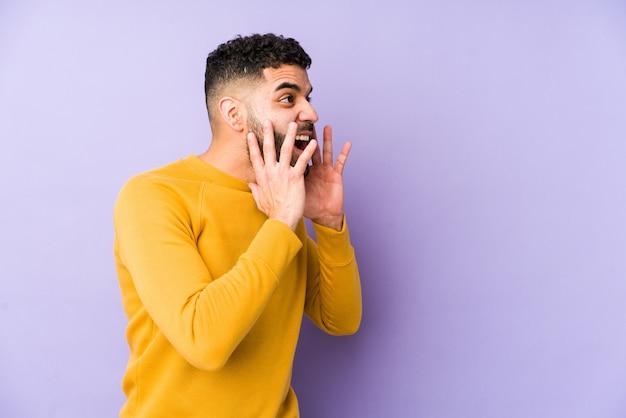 Giovane uomo arabo di razza mista isolato grida forte, tiene gli occhi aperti e le mani tese.