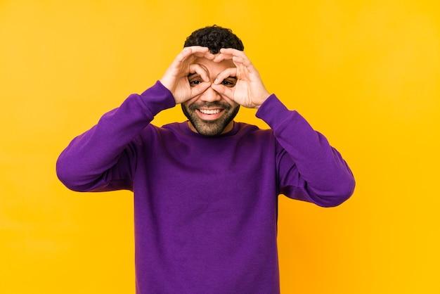 Giovane uomo arabo di razza mista isolato che mostra bene il segno sugli occhi