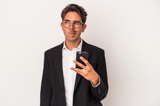 Giovane uomo d'affari di razza mista che tiene in mano un telefono cellulare isolato su sfondo bianco confuso, si sente dubbioso e incerto.