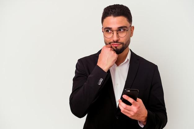 Giovane uomo d'affari di razza mista in possesso di un telefono cellulare uomo isolato su bianco rilassato pensando a qualcosa guardando uno spazio di copia.