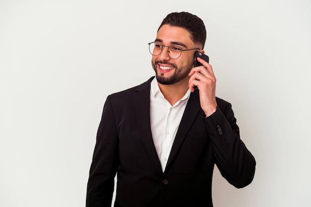 Giovane uomo d'affari di razza mista che tiene un telefono cellulare uomo isolato su bianco che mostra un gesto di chiamata di telefonia mobile con le dita.