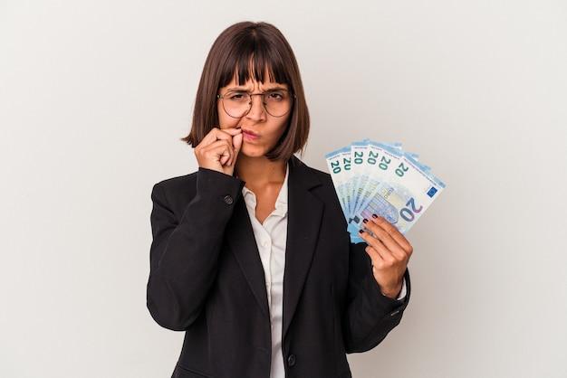 Giovane donna d'affari di razza mista in possesso di banconote isolate su sfondo bianco con le dita sulle labbra mantenendo un segreto.