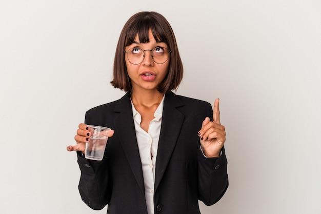 Giovane donna d'affari di razza mista in possesso di un bicchiere d'acqua isolato su sfondo bianco rivolto verso l'alto con la bocca aperta.