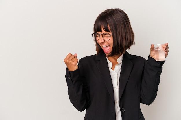 Giovane donna d'affari di razza mista in possesso di un bicchiere d'acqua isolato su sfondo bianco alzando il pugno dopo una vittoria, concetto di vincitore.