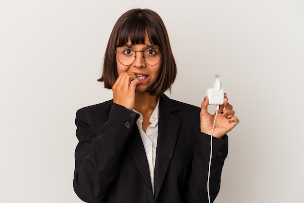Giovane donna di affari della corsa mista che tiene un caricatore del telefono isolato su fondo bianco che alza il pugno dopo una vittoria, concetto del vincitore.