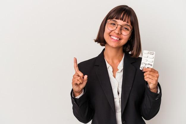 La giovane donna di affari della corsa mista che tiene le pillole ha isolato che mostra il numero uno con il dito.