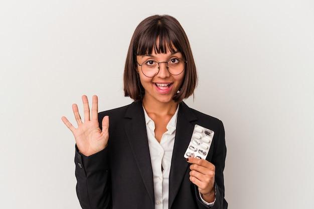 La giovane donna di affari della corsa mista che tiene le pillole ha isolato sorridente allegro che mostra numero cinque con le dita.