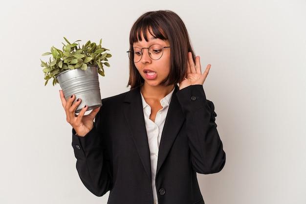 Giovane donna d'affari di razza mista in possesso di una pianta isolata su sfondo bianco cercando di ascoltare un pettegolezzo.