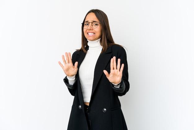 Giovane donna di affari di razza mista isolata su uno spazio bianco che rifiuta qualcuno che mostra un gesto di disgusto.