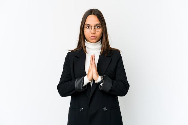 Giovane donna di affari di razza mista isolata sul muro bianco scioccata, che copre la bocca con le mani, ansiosa di scoprire qualcosa di nuovo.