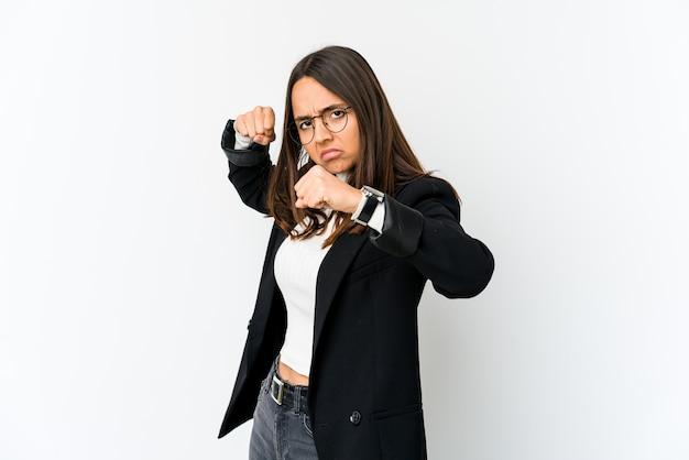 Giovane donna di affari di razza mista isolata sul muro bianco che lancia un pugno, rabbia, combattimenti a causa di un argomento, boxe.