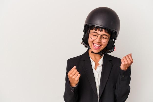Giovane donna d'affari di razza mista che indossa un casco da moto isolato alzando il pugno dopo una vittoria, concetto di vincitore.